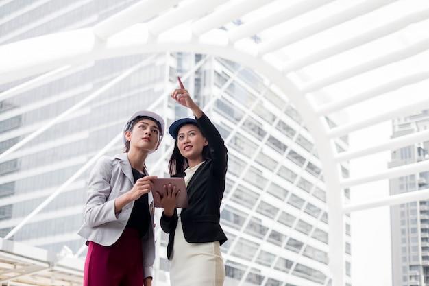 Zwei geschäftsfrauen, wirtschaftsingenieure, die an hand vor gebäude mit plan stehen