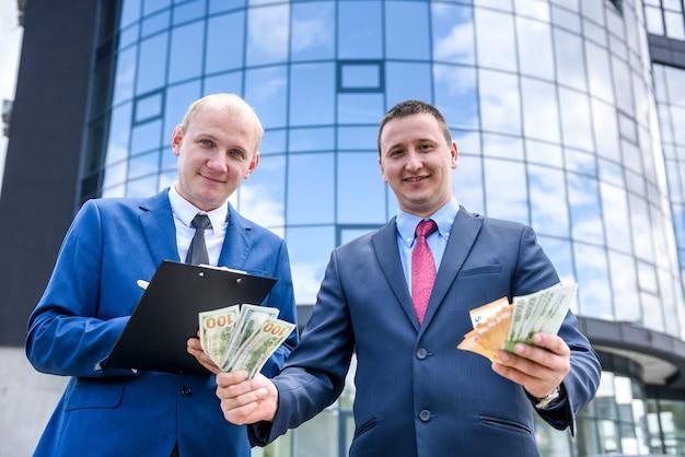 Zwei geschäftsleute, die dollar- und euro-banknoten zeigen