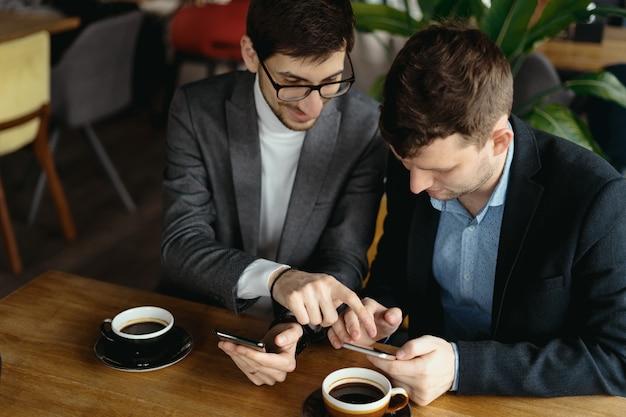 Zwei geschäftsleute, die ein gespräch mit einem smartphone führen