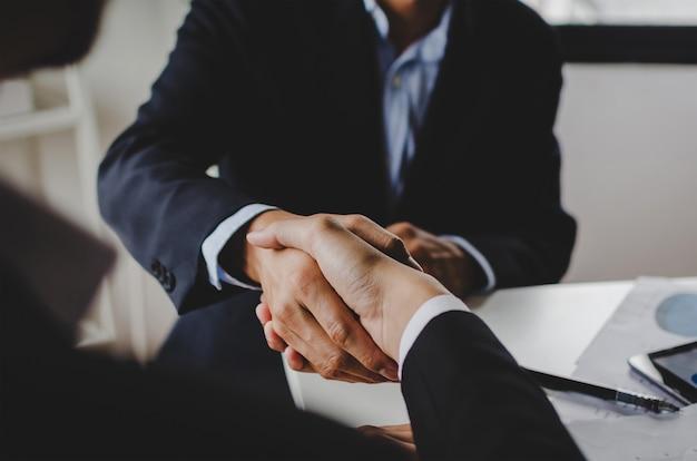 Zwei geschäftsleute, die hand schütteln, nachdem geschäft vertrag im konferenzzimmer im firmenbüro unterzeichnet hat