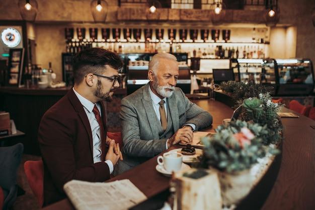 Zwei geschäftsleute, die im modernen café zusammenarbeiten.