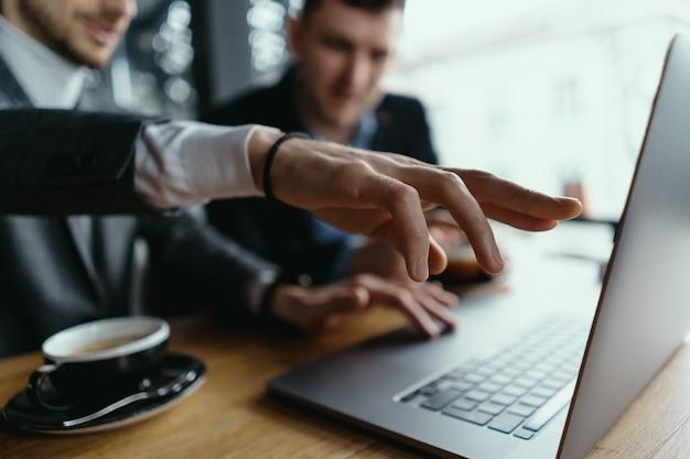 Zwei geschäftsleute, die laptop-bildschirm während der diskussion zeigen