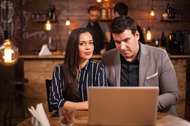 Zwei geschäftsleute, die sich in einem café treffen. arbeiten am laptop. geschäftliches gespräch.
