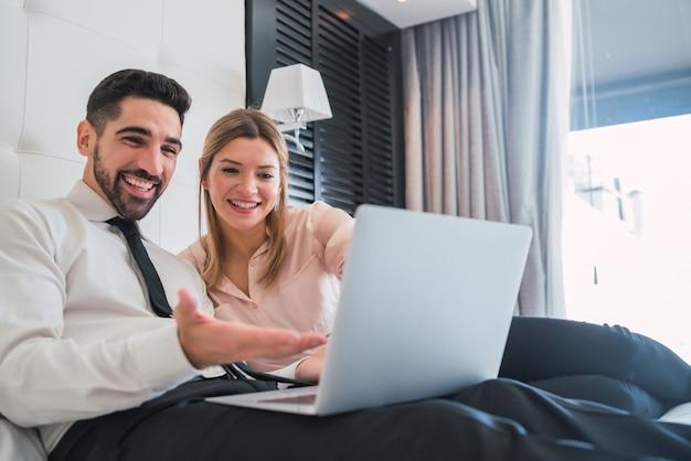 Zwei geschäftsleute, die zusammen an laptop arbeiten.
