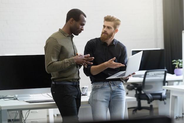 Zwei geschäftsleute, die zusammen auf laptop arbeiten