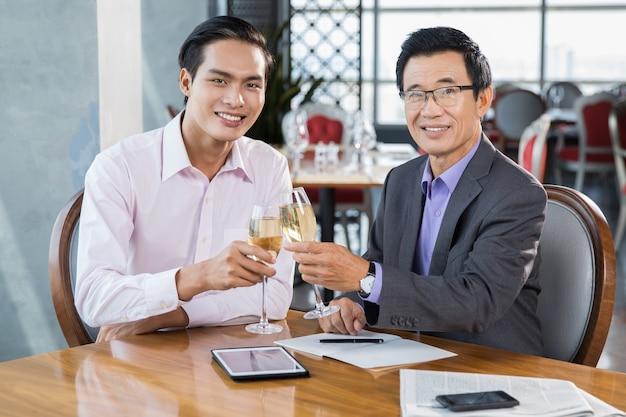 Zwei geschäftsleute feiern erfolg im restaurant