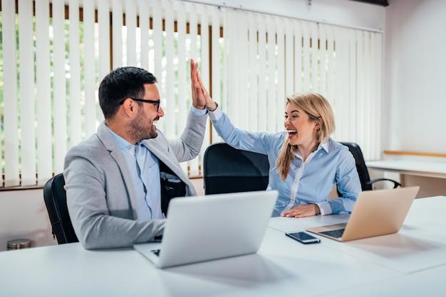 Zwei geschäftsleute high-five im hellen büro.