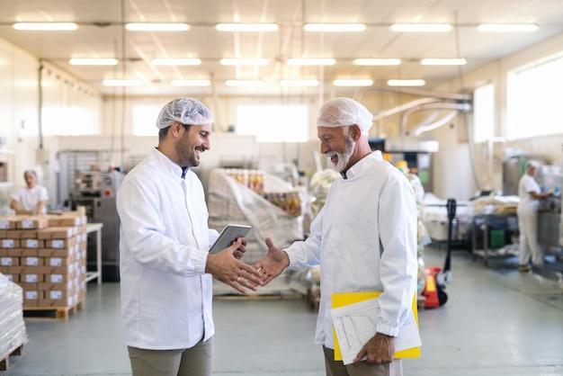 Zwei geschäftsleute in sterilen uniformen geben sich die hand für gute arbeit, während sie in der lebensmittelfabrik stehen. älterer ordner und grafiken, während jüngeres tablett.