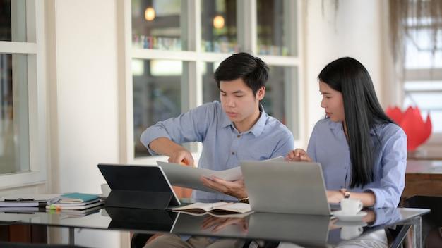 Zwei geschäftsleute informieren sich in einem einfachen arbeitsbereich über ihr projekt