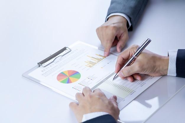 Zwei geschäftsleute oder analysten bewerten den abschlussbericht über return on investment