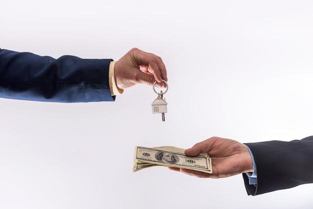 Zwei geschäftsleute schließen einen kauf- oder mietvertrag für ein haus ab, in dem sie dollars und schlüssel für die wohnung austauschen. verkauf nach hause