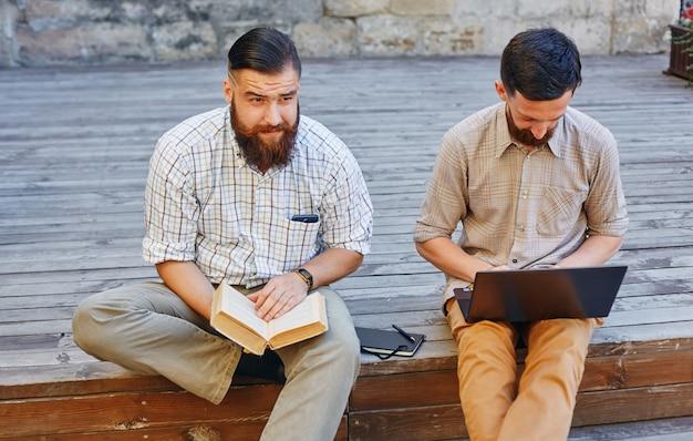 Zwei geschäftsleute sitzen auf holzoberfläche und arbeiten kreativ