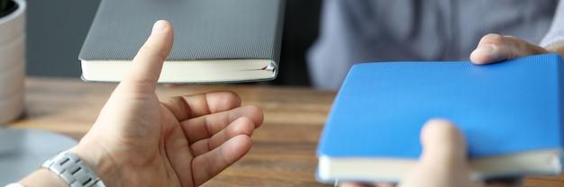 Zwei geschäftsleute tauschen mit notizbüchern am büroarbeitsplatz aus