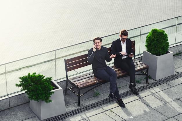 Zwei geschäftsleute unterhalten sich auf der straßenbank, die mit telefon und tablet beschäftigt ist.
