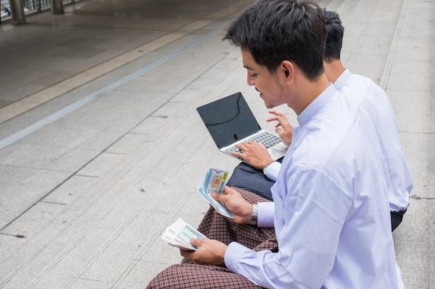 Zwei geschäftsleute von myanmar, die bargeld zählen und mit laptop in der stadt arbeiten