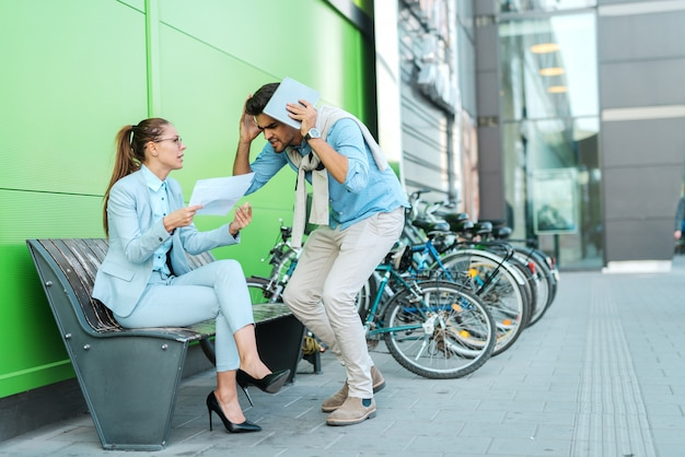 Zwei geschäftsleute zogen sich elegant an und stritten sich im freien über das projekt. mann, der tablette hält, während frau papierkram hält und auf einer bank sitzt.