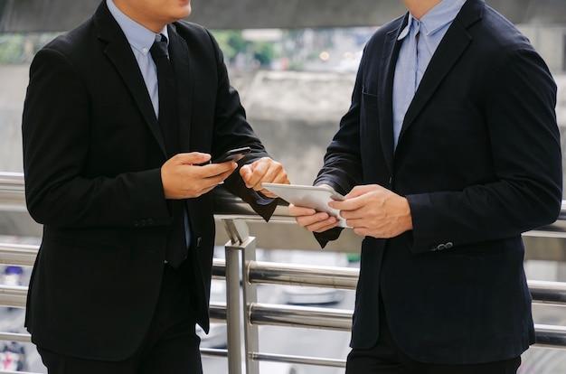 Zwei geschäftsmann, der informationen über finanznachrichten spricht und liest