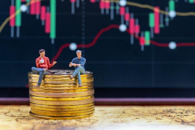 Zwei geschäftsmann-miniaturfigur, die auf einem stapel von gold-bitcoin-münzen mit candlestick-chart sitzt
