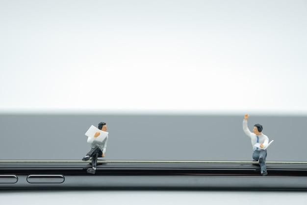 Zwei geschäftsmannminiaturzahlen, die ein buch sitzen und lesen und am intelligenten telefon sprechen.