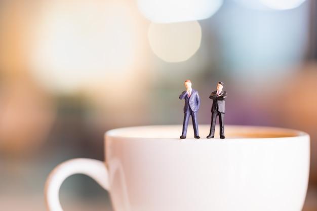 Zwei geschäftsmannminiaturzahlen stehen und denken auf weißer platte der schale heißen kaffees.