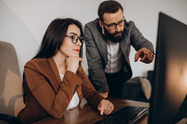 Zwei geschäftspartner arbeiten im büro am computer zusammen