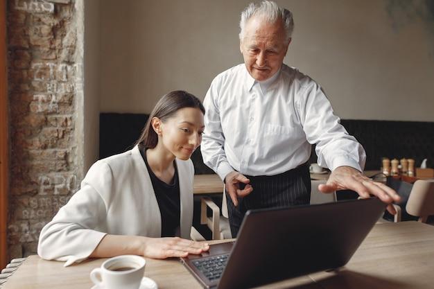 Zwei geschäftspartner arbeiten mit einem laptop in einem café