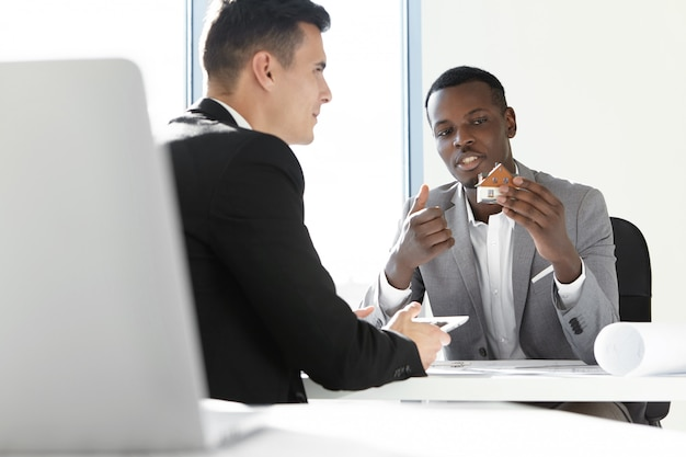 Zwei geschäftspartner treffen sich im büro: afrikanischer mann im grauen anzug, der ein maßstabsgetreues modellhaus hält, details seines außendesigns erklärt und mit seinem kollegen am schreibtisch mit blaupausen sitzt