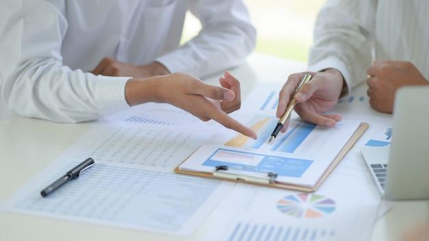 Zwei geschäftsteams diskutieren und analysieren die diagramme der projektarbeit im büro.