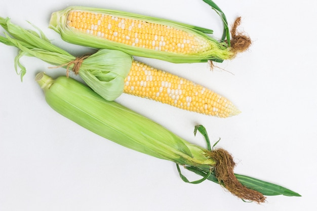 Zwei geschälte maiskolben. ungeschälte maiskolben mit blättern. weißer hintergrund. flach legen