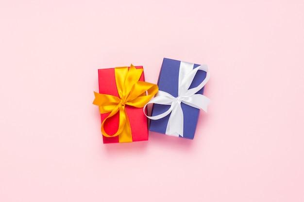 Zwei geschenkboxen auf einem rosa hintergrund. urlaubskonzept
