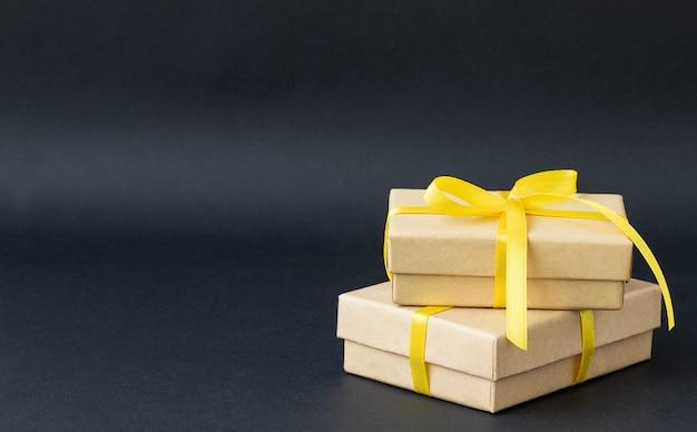 Zwei geschenkboxen mit gelbem band auf schwarzem hintergrund