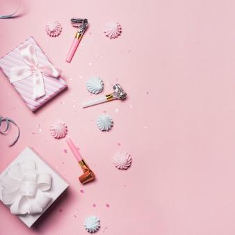 Zwei geschenkboxen mit schlagsahne; konfetti und party gebläse auf rosa hintergrund