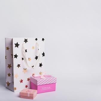 Zwei geschenkboxen und einkaufspapiertüte auf weißem hintergrund