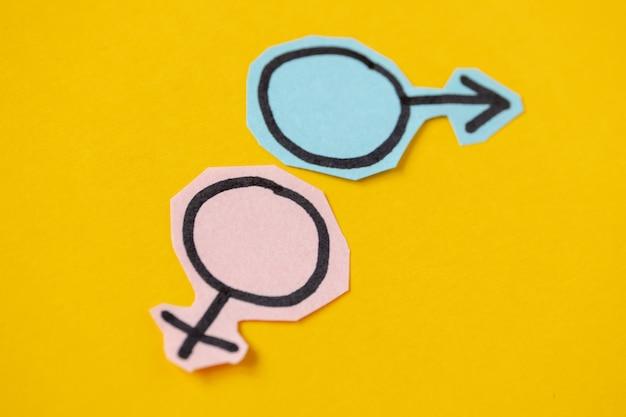 Zwei geschlechtssymbole venus und mars aus blauem und rosa papier geschnitten