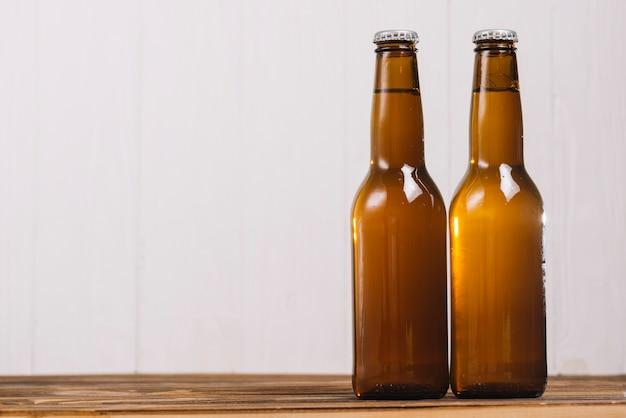 Zwei geschlossene bierflaschen auf hölzernem schreibtisch
