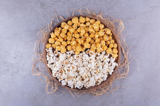 Zwei geschmacksrichtungen von popcorn, serviert auf einem holztablett, das mit stroh auf marmorhintergrund dekoriert ist. foto in hoher qualität