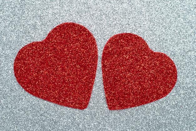 Zwei geschnitzte rote herzen auf einer grau glänzenden wand. bastelpapier, glitzer, funkelnde textur. liebeskonzept.
