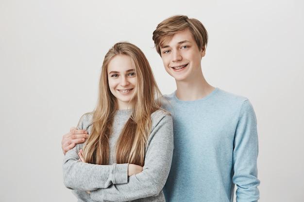 Zwei geschwister, die in die kamera lächeln. schwester und bruder mit umarmten hosenträgern