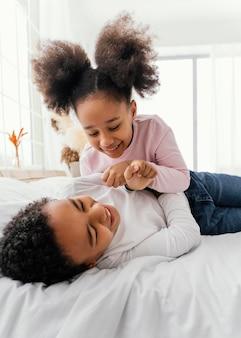 Zwei geschwister, die zu hause im bett zusammen spielen