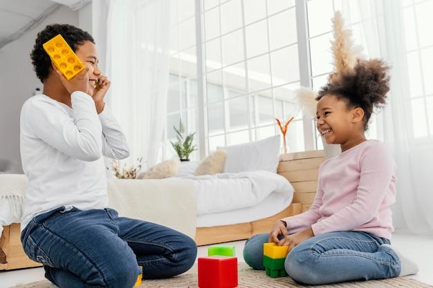 Zwei geschwister, die zu hause mit spielzeug zusammen spielen