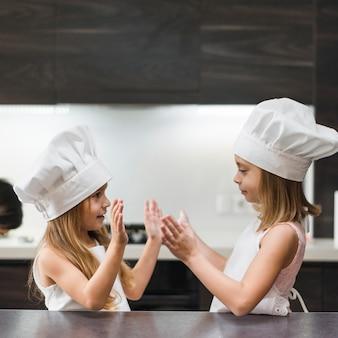 Zwei geschwister im chefhut und -schutzblech, die küche spielen