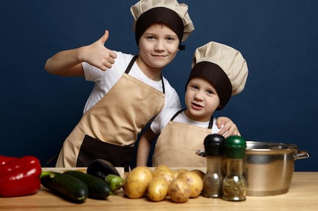 Zwei geschwistergeschwister in kochuniform, die das abendessen in der küche vorbereiten: selbstbewusster junge, der daumen hoch zeigt und seinen kleinen bruder umarmt, bereit, aus frischem bio-gemüse eine köstliche mahlzeit zuzubereiten