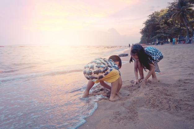 Zwei geschwisterkinder spielen mit welle und sand in pattaya-strand thailand