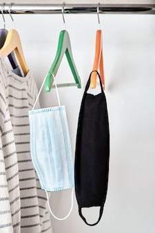 Zwei gesichtsmasken hängen im kleiderschrank am kleiderbügel zusammen mit freizeitkleidung