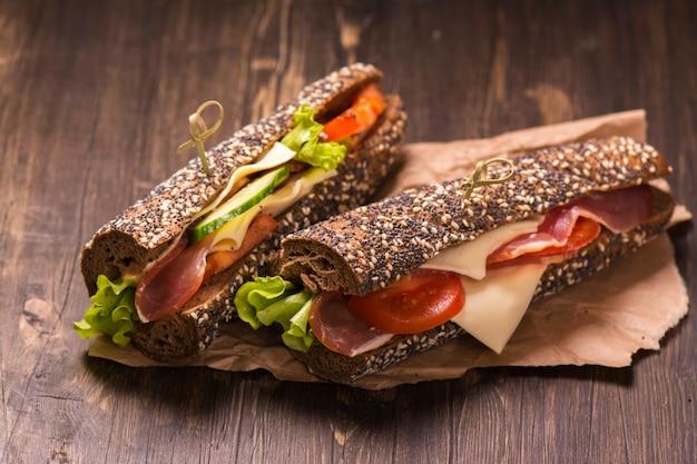 Zwei gesunde sandwiches mit schinken, käse und gemüse