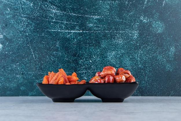 Zwei getrocknete bio-früchte auf schwarzem teller auf steinhintergrund.