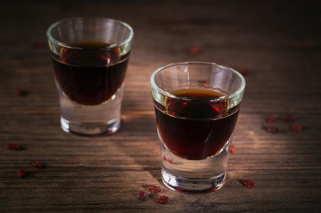 Zwei gläser alkoholisches getränk auf dunklem holzhintergrund. kräuterbitterlikör mit verschiedenen natürlichen zutaten.