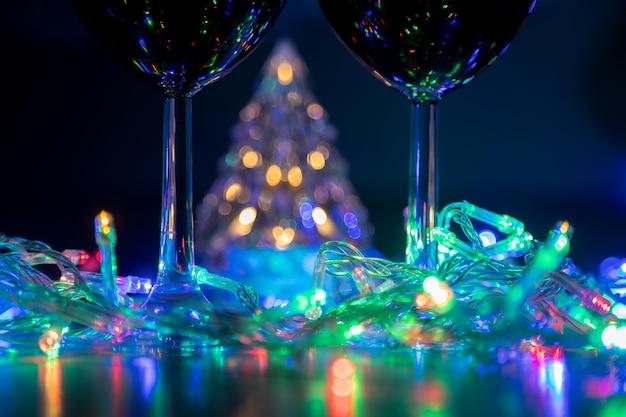 Zwei gläser auf dem hintergrund eines leuchtenden weihnachtsbaums und einer bunten girlande in einer dunklen nacht