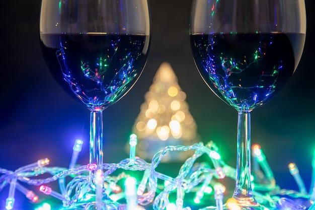 Zwei gläser auf dem hintergrund eines leuchtenden weihnachtsbaums und einer mehrfarbigen girlande auf dunklem nachthintergrund. neujahr feierlichkeiten...