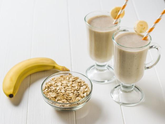 Zwei gläser bananen-smoothie mit haferflocken